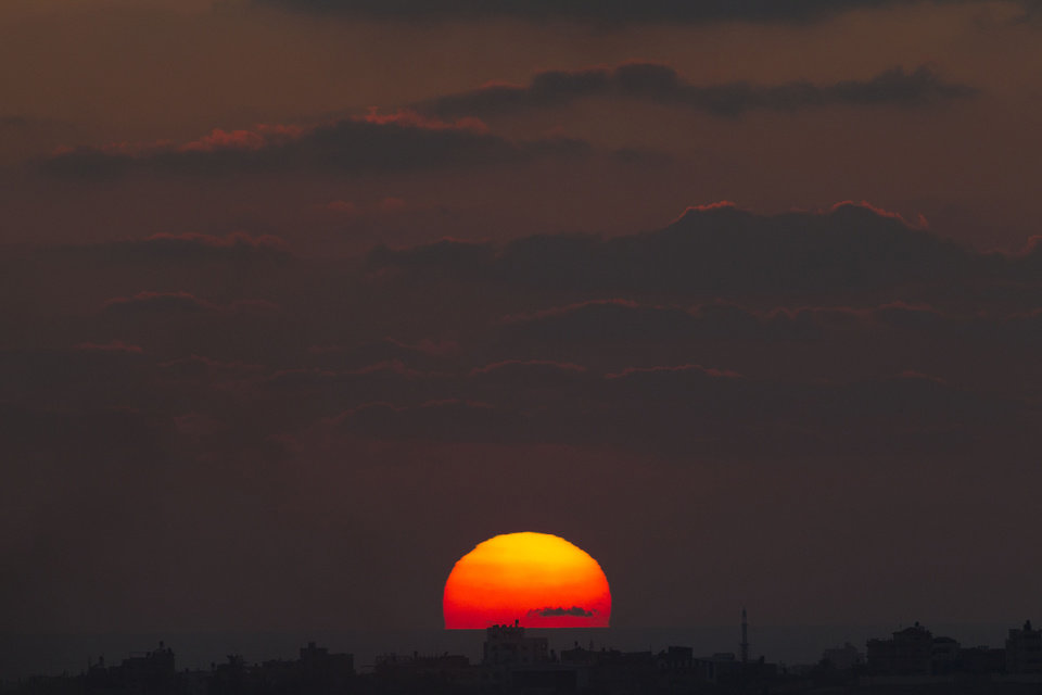 Photo - The sun sets behind the Gaza Strip as seen from the Israel Gaza border on Wednesday, July 16, 2014. (AP Photo/Ariel Schalit)