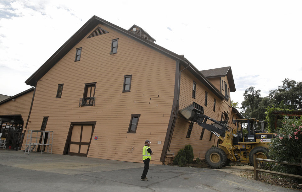 Photo - Construction manager Joe Griego looks at the heavy equipment brought in to support the leaning earthquake damaged historic winery building at Trefethen Family Vineyards Friday, Aug. 29, 2014, in Napa, Calif. Harvest resumed at the winery on Friday in addition to the arrival of crews to shore up the historic building that dates from 1886. The 6.0-earthquake that damaged buildings and left scores of people injured in California's wine country was the largest temblor to hit the San Francisco Bay Area since the 6.9-magnitude Loma Prieta earthquake in 1989. (AP Photo/Eric Risberg)