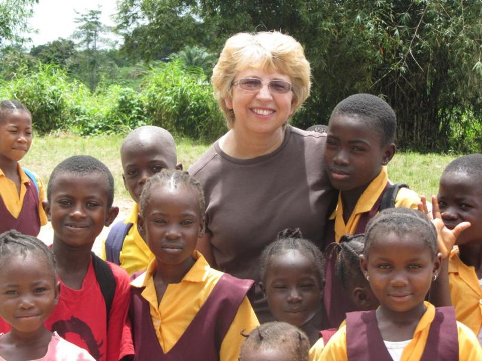 Photo - This Oct. 7, 2013 photo provided by Jeremy Writebol show his mother, Nancy Writebol, with children in Liberia. Writebol is one of two Americans working for a missionary group in Liberia that have been diagnosed with Ebola. Plans are underway to bring back the two Americans from Africa for treatment. (AP Photo/Courtesy Jeremy Writebol)