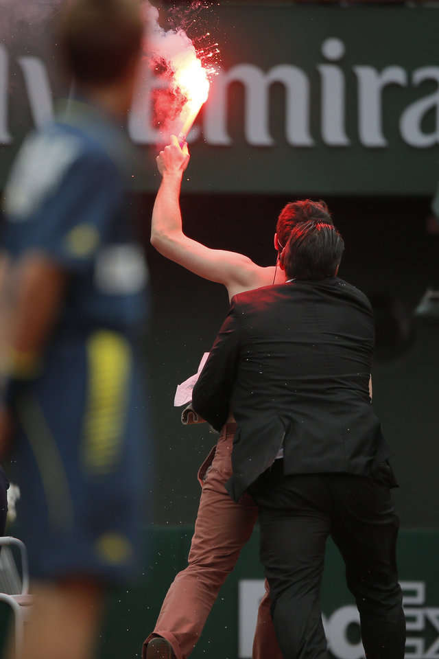 Photo - A ball boy watches a security guard remove a demonstrator who ran onto center court as Spain's Rafael Nadal played against compatriot David Ferrer in the final of the French Open tennis tournament, at Roland Garros stadium in Paris, Sunday June 9, 2013. (AP Photo/Michel Spingler)