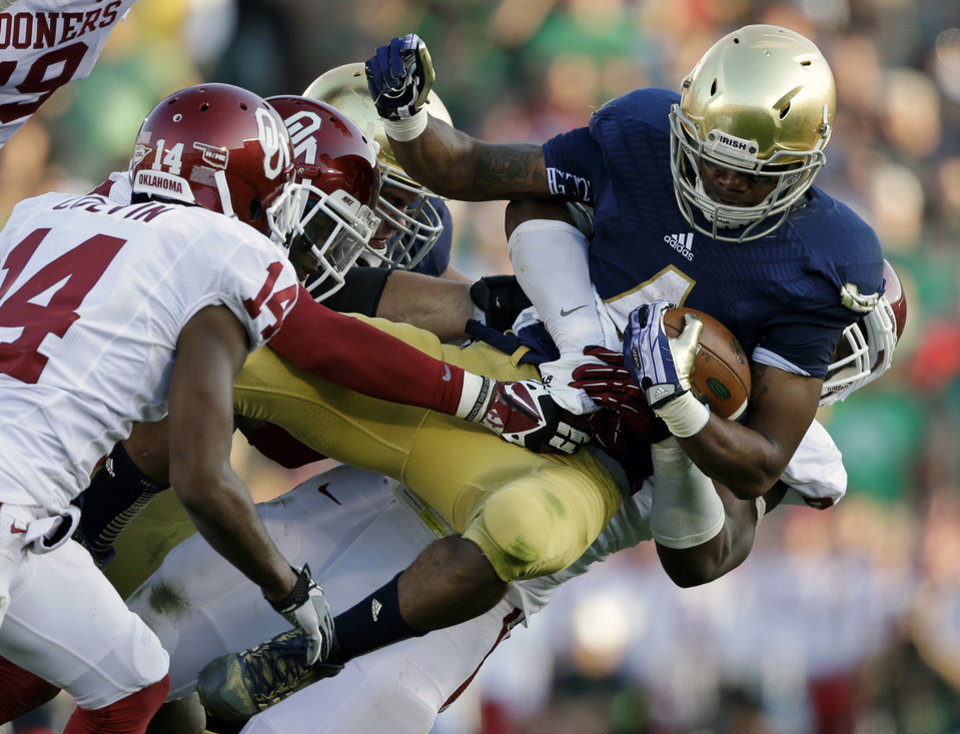 Photo - Notre Dame's George Atkinson III (4) is tackled by Oklahoma's Geneo Grissom, behind, during the second half of an NCAA college football game on Saturday, Sept. 28, 2013, in South Bend, Ind. Oklahoma defeated Notre Dame 35-21. (AP Photo/Darron Cummings) ORG XMIT: INDC120