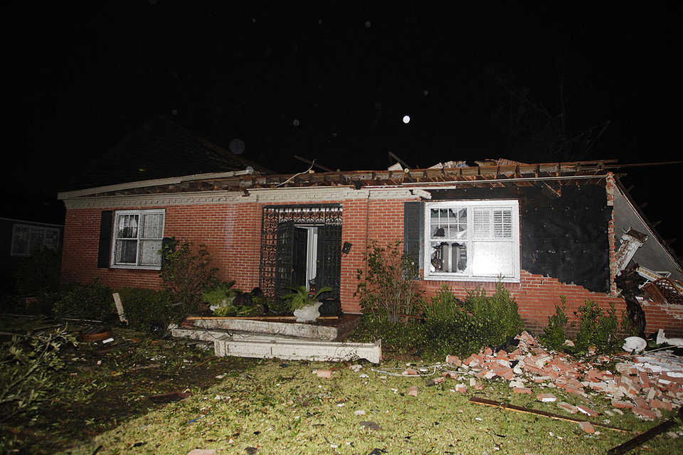 Photo - A home in the Midtown section of Mobile, Ala. is damaged after a tornado touched down Tuesday, Dec. 25, 2012. A Christmas Day twister outbreak left damage across the Deep South while holiday travelers in the nation's much colder midsection battled sometimes treacherous driving conditions from freezing rain and blizzard conditions. (AP Photo/AL.com, Mike Kittrell)  MAGS OUT