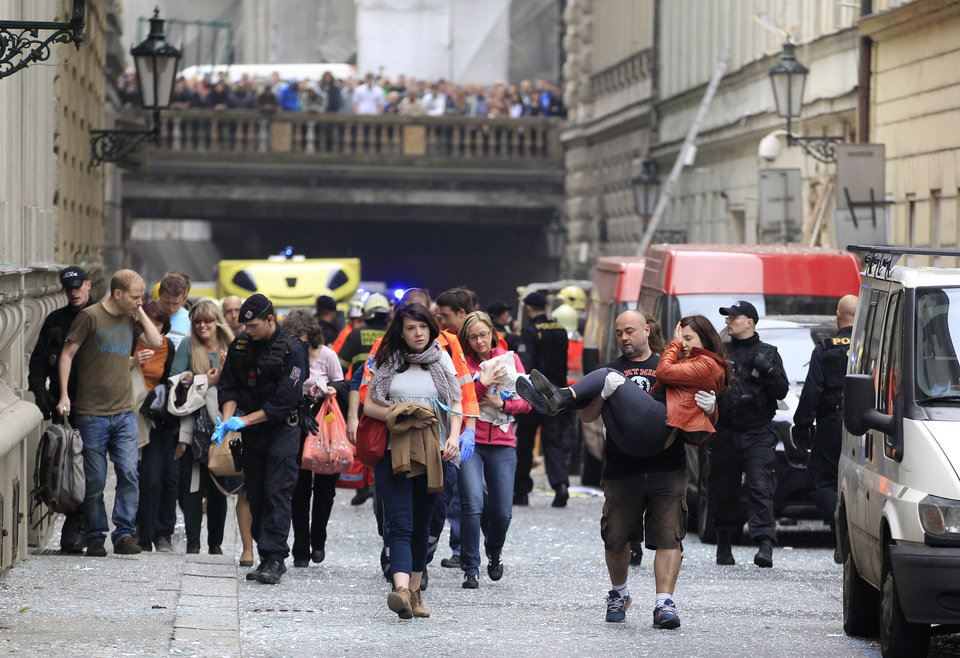 Photo - Injured people leave a scene of an explosion in downtown Prague, Czech Republic, Monday, April 29, 2013. Police said a powerful explosion has damaged a building in the center of the Czech capital and they believe some people are buried in the rubble. (AP Photo/Petr David Josek)