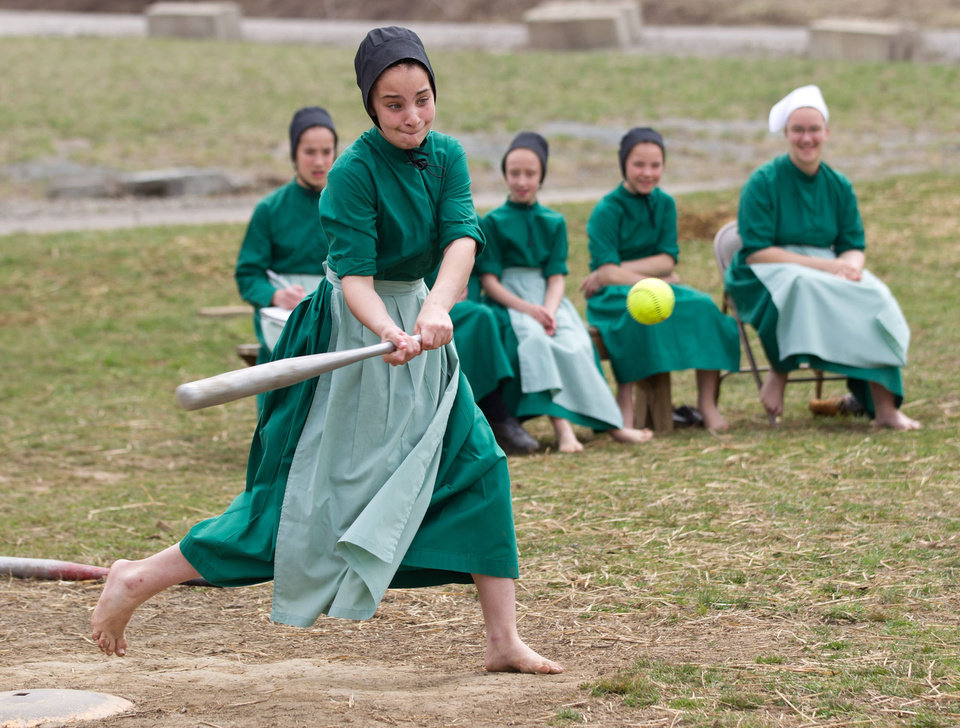 Amish girls play softball after class during an end of the school year celebration on Tuesday, April 9, 2013 in Bergholz, Ohio. The celebration was also part of a farewell picnic for those sentenced in the hair and beard cutting scandal earlier in the year. (AP Photo/Scott R. Galvin)