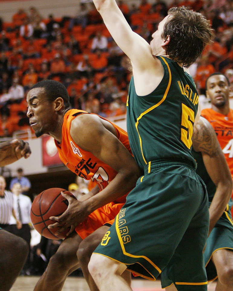 Photo - OSU's Markel Brown (22) tries to get the ball past Brady Heslip (5) of Baylor in the second half of a men's college basketball game between the Oklahoma State University Cowboys and the Baylor University Bears at Gallagher-Iba Arena in Stillwater, Okla., Saturday, Feb. 4, 2012. Baylor beat OSU, 64-60. Photo by Nate Billings, The Oklahoman