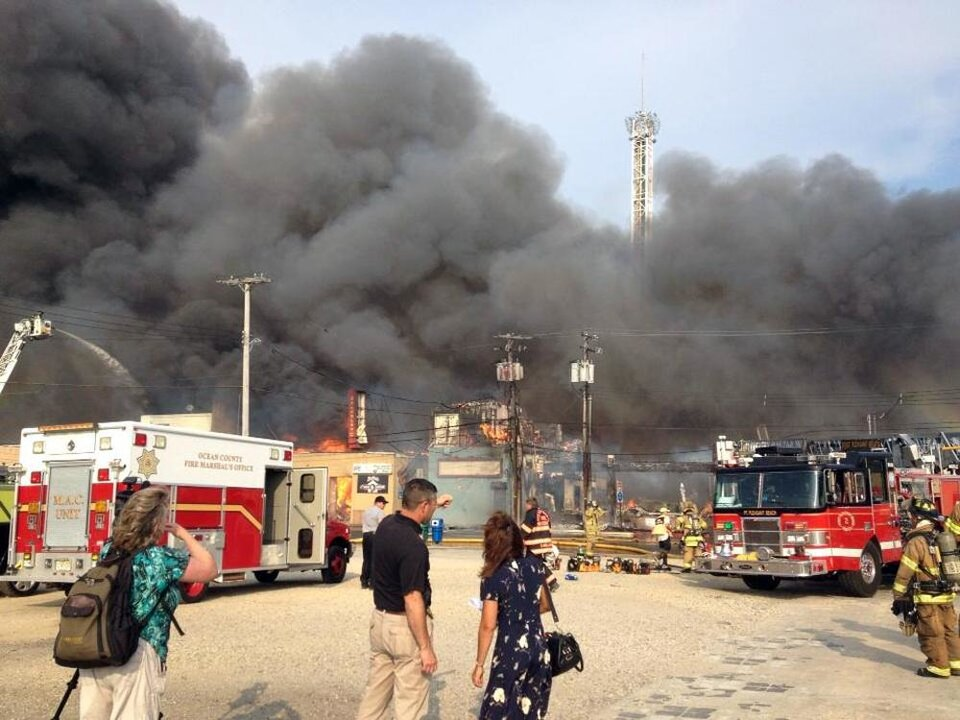 Photo - Firefighters battle a raging fire on the boardwalk in Seaside Heights, N.J. that apparently started in an ice cream shop and has spread several blocks down, Thursday, Sept. 12, 2013. The boardwalk was damaged in Superstorm Sandy and was being repaired. (AP Photo/The Asbury Park Press, Erik Larsen)  MANDATORY CREDIT: PAPER AND PHOTOGRAPHER; NO SALES