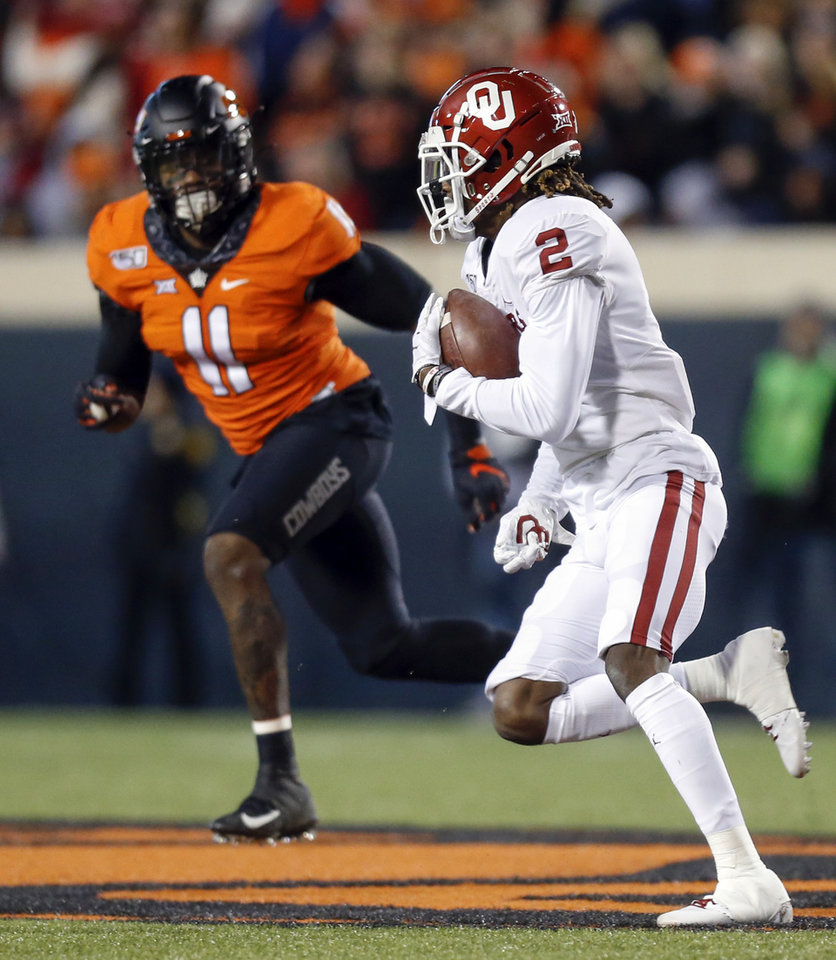 Photo - Oklahoma's CeeDee Lamb (2) carries the ball as Oklahoma State's Amen Ogbongbemiga (11) defends during the Bedlam college football game between the Oklahoma State Cowboys (OSU) and Oklahoma Sooners (OU) at Boone Pickens Stadium in Stillwater, Okla., Saturday, Nov. 30, 2019. [Nate Billings/The Oklahoman]