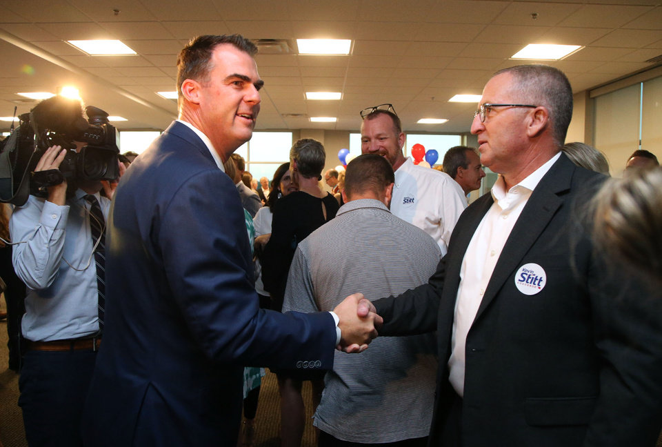 Photo - Gubernatorial candidate Kevin Stitt (left) greets supporter Ed Stanton during a watch party in Jenks, Okla., on Tuesday, August 28, 2018. MATT BARNARD/Tulsa World