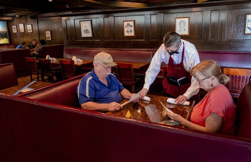Photo - Waiter Tommy Terrell greets customers Len and Lynda Landrith as they arrive for lunch at Cattlemen's Steakhouse in Oklahoma City, Okla. on Friday, May 1, 2020. Cattlemen's and other restaurants begin their gradual reopening on Friday after being closed due to the Coronavirus Pandemic.[Chris Landsberger/The Oklahoman]