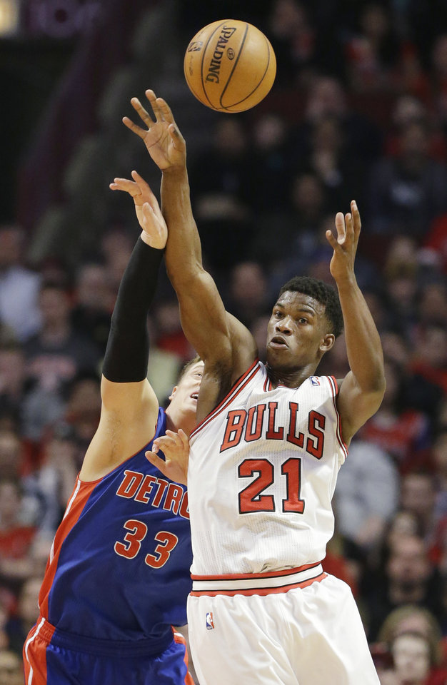 Photo - Chicago Bulls guard Jimmy Butler, right, battles for a rebound against Detroit Pistons forward Jonas Jerebko, of Sweden, during the first half of an NBA basketball game in Chicago, Sunday, March 31, 2013. (AP Photo/Nam Y. Huh)