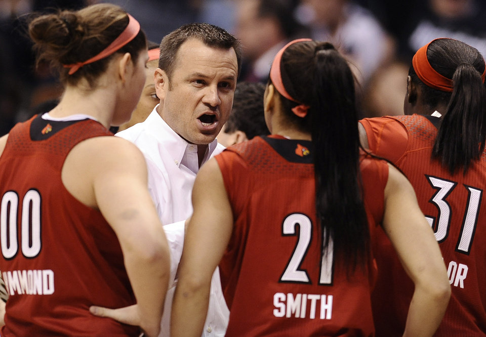 Photo - Louisville head coach Jeff Walz, center, talks with Louisville's Sara Hammond (00), Bria Smith (21), and Asia Taylor (31) during the first half of an NCAA women's college basketball game in the finals of the American Athletic Conference  basketball tournament, Monday, March 10, 2014, in Uncasville, Conn. (AP Photo/Jessica Hill)