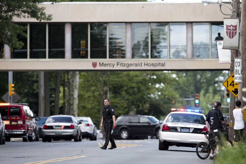 Photo - An officer directs traffic near the scene of a shooting Thursday, July 24, 2014, at a wellness center attached to Mercy Fitzgerald Hospital in Darby, Pa. A doctor grazed by gunfire from a patient who had entered his office in a suburban hospital's psychiatric unit stopped him by returning fire with his own gun and injuring him, authorities said. (AP Photo)