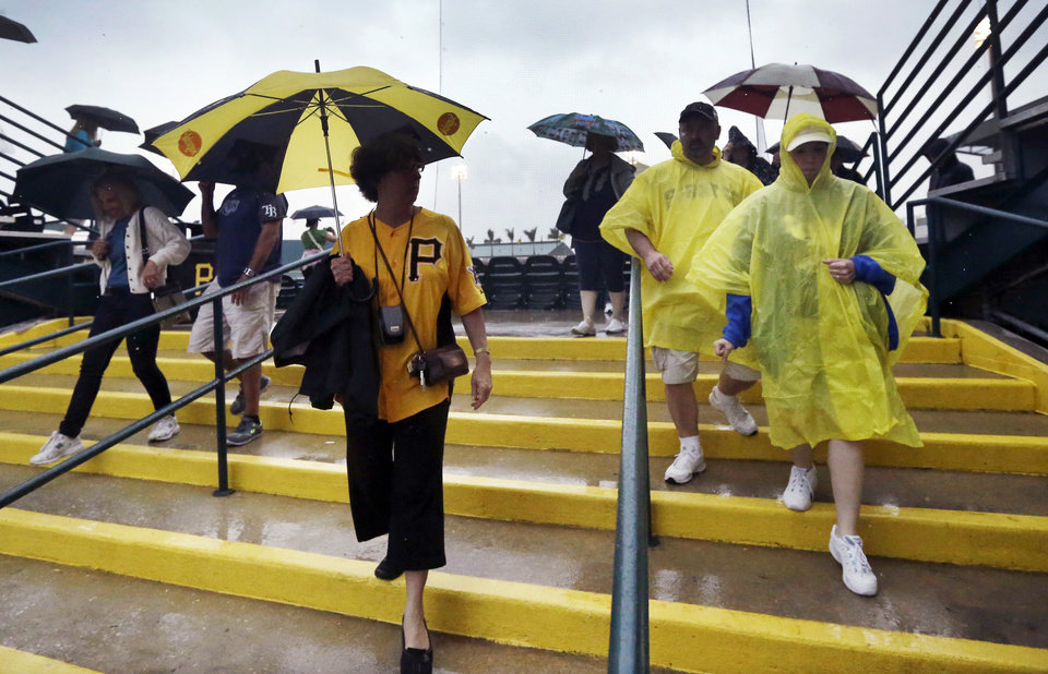 Photo - Baseball fans leave the spring exhibition baseball game between the Pittsburgh Pirates and the New York Yankees after being called due to rain in Bradenton, Fla., Monday, March 17, 2014. (AP Photo/Carlos Osorio)