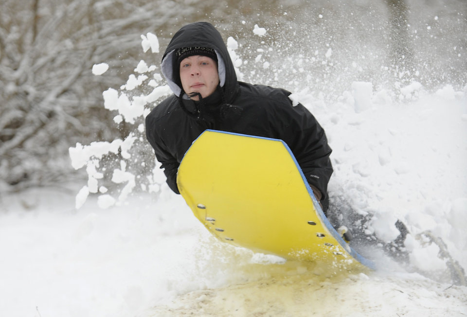 Photo - Penn State University student Andrew Bachman jumps his sled at Slab Cabin Park, in State College, Pa . Thursday, Dec. 27, 2012. The cleanup continues after a major winter storm hit Centre County Wednesday.  (AP Photo/Centre Daily Times, Nabil K. Mark)