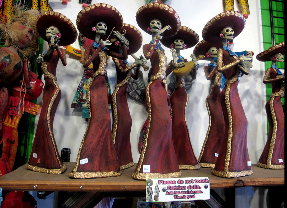Photo - In this May 8, 2013 photo, artwork is shown at Masks y Mas, an Albuquerque shop that sells 'Day of the Dead' art year round. Disney announced Tuesday that it was a withdrawing a