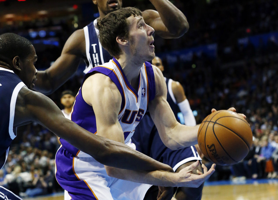 Oklahoma City Thunder forward Kevin Durant, left, reaches in and knocks the ball away from Phoenix Suns guard Goran Dragic, right, in the first quarter of an NBA basketball game in Oklahoma City, Monday, Dec. 31, 2012. (AP Photo/Sue Ogrocki)