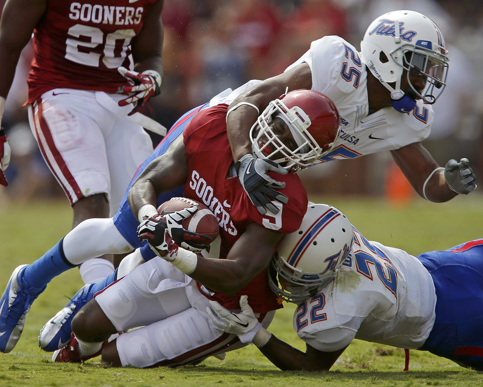 Photo - Oklahoma's Gabe Lynn (9) is brought down by Tulsa's Ja'Terian Douglas (25) and Trey Watts (22) after an interception during a college football game between the University of Oklahoma Sooners (OU) and the Tulsa Golden Hurricane at Gaylord Family-Oklahoma Memorial Stadium in Norman, Okla., on Saturday, Sept. 14, 2013. Oklahoma won 51-20. Photo by Bryan Terry, The Oklahoman