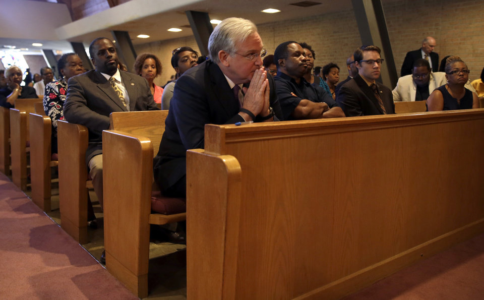 Photo - Missouri Gov. Jay Nixon, center, listens during a meeting of clergy and community members held to discuss law enforcement's response to demonstrations over the killing of Michael Brown Thursday, Aug. 14, 2014, in Florissant, Mo. Nixon says