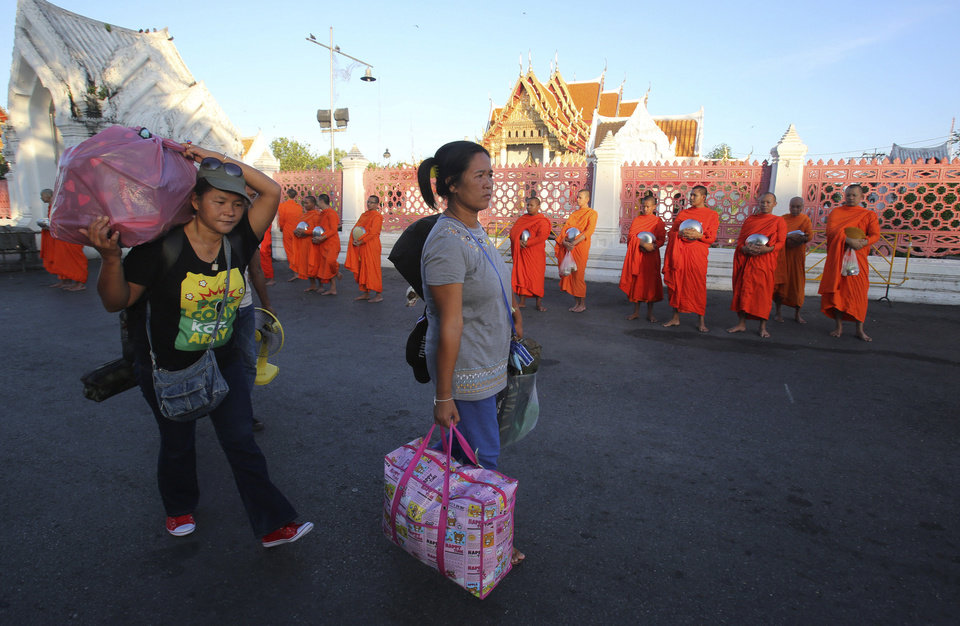 Photo - Anti-government demonstrators with their belongings leave a demonstration site past Buddhist monks in Bangkok, Thailand, Friday, May 23, 2014, a day after soldiers staged a coup. Thailand's ruling military made its first order of the day summoning members of the politically influential family to a meeting Friday morning, a day after it seized control of this volatile Southeast Asian nation in a bloodless coup. (AP Photo/Sakchai Lalit)
