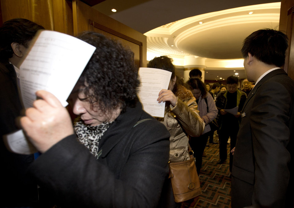 Photo - Chinese relatives of passengers aboard a missing Malaysia Airlines plane use application documents to block their faces as they walk out of a hotel room in Beijing Monday, March 10, 2014. The anguished hours had turned into a day and a half. Fed up with awaiting word on the missing plane, relatives of passengers in Beijing lashed out at the carrier with a handwritten ultimatum and an impromptu news conference. (AP Photo/Andy Wong)