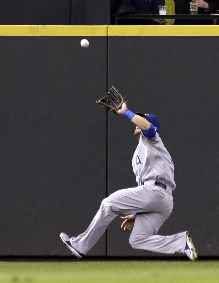 Photo - Kansas City Royals left fielder Alex Gordon skids toward a deep fly ball from Seattle Mariners' Raul Ibanez in the fifth inning of a baseball game Wednesday, Sept. 25, 2013, in Seattle. Gordon made the catch. (AP Photo/Elaine Thompson)