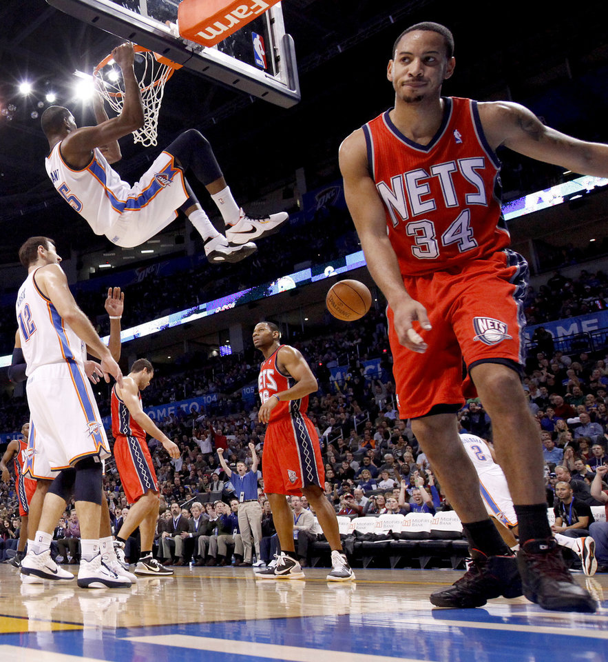 Photo - Oklahoma City's Kevin Durant hangs on the rim after a dunk as New Jersey's Kris Humphries, left, Stephen Graham, and Devin Harris react during the NBA basketball game between the Oklahoma City Thunder and the New Jersey Nets at the Oklahoma City Arena, Wednesday, Dec. 29, 2010.  Photo by Bryan Terry, The Oklahoman