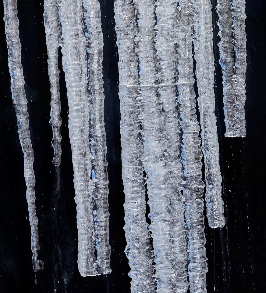 Photo - Long icicles hanging from an eave drape a building's windows. Central Oklahoma residents began digging out from beneath nearly a foot of snow covering the ground Wednesday, Feb, 2, 2011, after yesterday's winter snowstorm. Photo by Jim Beckel, The Oklahoman