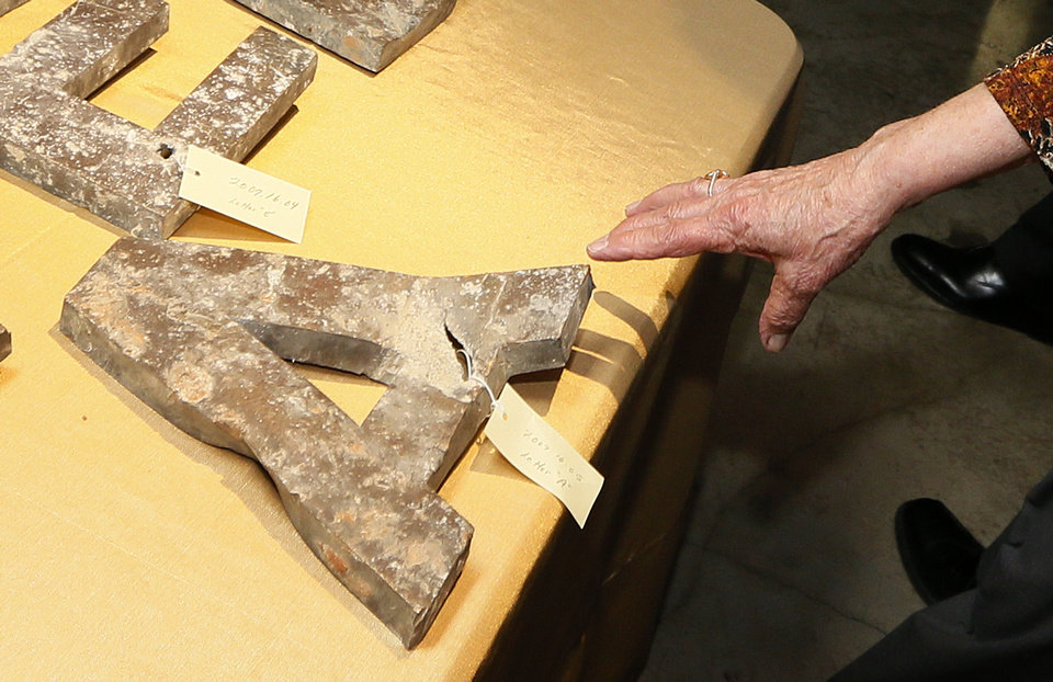 Survivor Florence Rogers holds her hand over one of the letters recovered in the rubble that used to hang on the exterior and identify the Alfred P. Murrah Federal Building. NATE BILLINGS - NATE BILLINGS