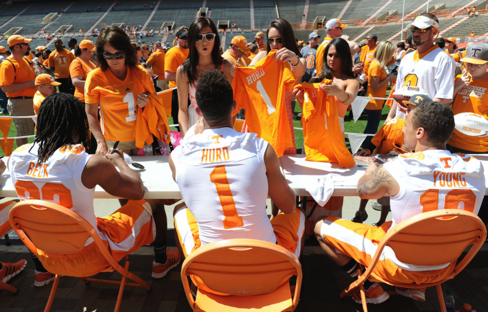 Photo - Tennessee running backs, from left, Chris Beck, Jalen Hurd and Devrin Young, sign autographs during fan day at Neyland Stadium in Knoxville, Tenn., Saturday, April 12, 2014. The event gave fans the opportunity to greet players and obtain autographs before the Orange and White spring football game. (AP Photo/Knoxville News Sentinel, Amy Smotherman Burgess)