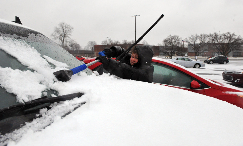Photo - Tiffany Collins removes snow from her windshield as rain and sleet continues to fall in downtown Evansville, Ind., Tuesday, Feb. 4, 2014.  A Winter Storm Warning was issued Tuesday as a mixture of snow, sleet and rain continued into the evening with temperatures around 30 degrees. (AP Photo/The Evansville Courier & Press, Jason Clark)