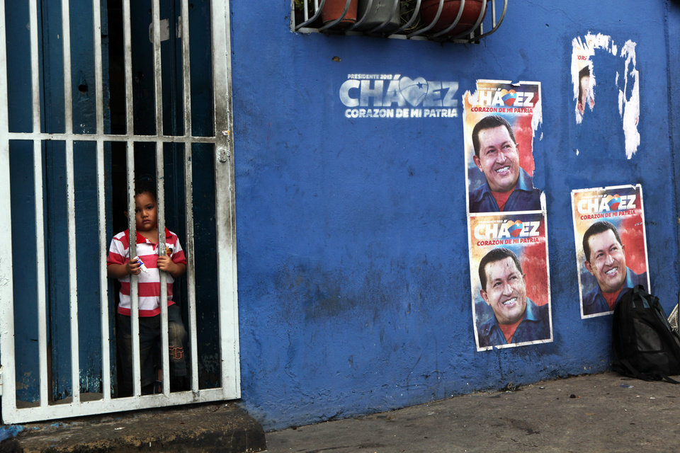 Santiago, 2, peeks out from the gate on his home's doorway where posters of Venezuela's President Hugo Chavez cover a wall in Caracas, Venezuela, Friday, Oct. 5, 2012. Venezuelans will head to the polls Sunday to vote in their country's presidential election, deciding on whether to keep Chavez or seek change. (AP Photo/Rodrigo Abd)