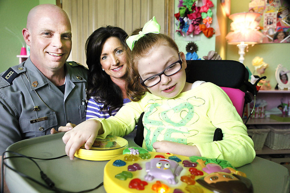 Photo - Mike and Brenda Greene pose with their daughter Macie, 9, who has Rett syndrome. PhotoS By David McDaniel, The Oklahoman