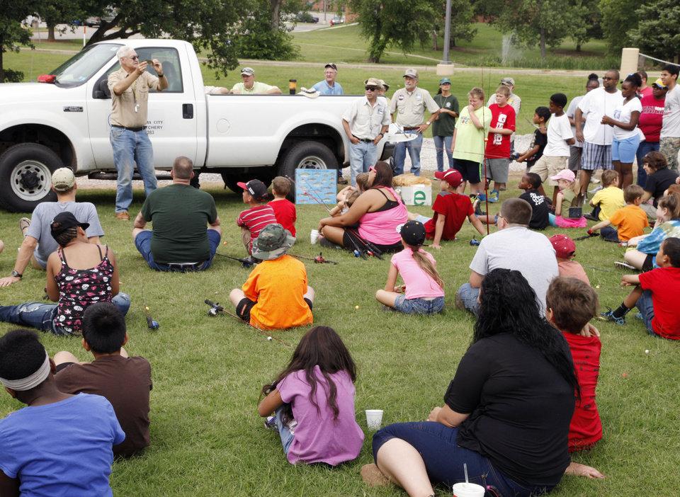Photo -  Fisheries biologist Bob Martin talks to children during the Oklahoma City Parks and Recreation Department's Hooked on Fishing event at Metro Tech. Photo by Paul Hellstern, The Oklahoman   PAUL HELLSTERN -