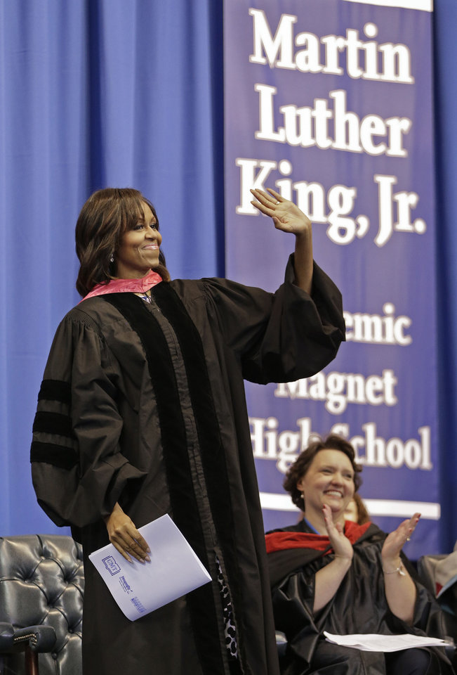 First lady Michelle Obama is introduced to deliver the commencement address to graduates of Martin Luther King, Jr. Academic Magnet High School on Saturday, May 18, 2013, in Nashville, Tenn. At right is teacher Carmen Mullins. (AP Photo/Mark Humphrey)