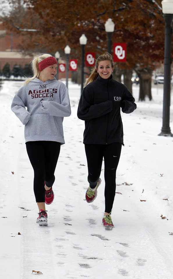 University of Oklahoma students Megan Thompson, left, and Sarah Wible jog in the snow on campus on Friday, Dec. 6, 2013 in Norman, Okla. Photo by Steve Sisney, The Oklahoman