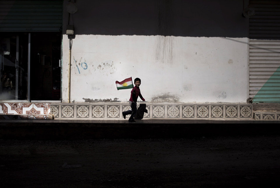 Photo - A boy runs as he holds a Kurdish flag in Ras al-Ayn, Syria, Wednesday, Feb. 27, 2013. The U.N. says more than 70,000 people have been killed since Syria's civil war started in March 2011. (AP Photo/Manu Brabo)