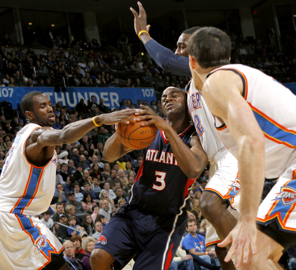 Photo - Oklahoma City's Serge Ibaka (left) Jeff Green and Nick Collison pressure Atlanta's Damien Wilkins during their NBA basketball game at the OKC Arena in Oklahoma City on Friday, Dec. 31, 2010. The Thunder beat the Hawks 103-94. Photo by John Clanton, The Oklahoman