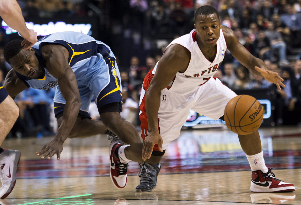 Photo - Toronto Raptors guard Kyle Lowry, right, moves past Memphis Grizzlies guard Tony Allen, left, during first half NBA basketball action in Toronto on Friday, March. 14, 2014. (AP Photo/The Canadian Press, Nathan Denette)