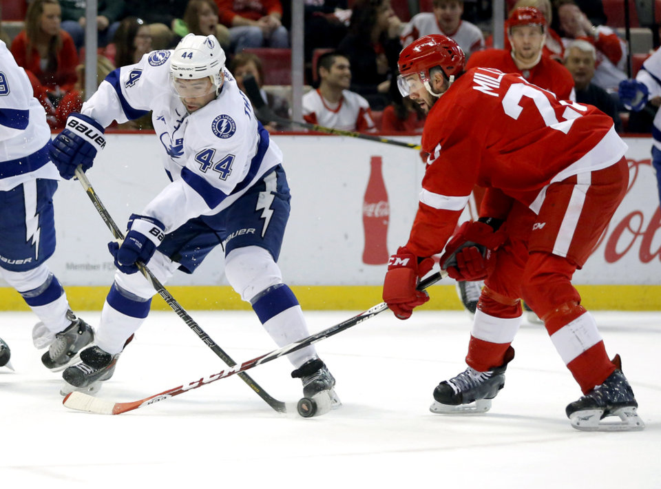 Photo - Tampa Bay Lightning's Nate Thompson (44) has his stick blocked by Detroit Red Wings' Drew Miller (20) while trying to take a shot on goal during the first period of an NHL hockey game, Sunday, March 30, 2014, in Detroit. (AP Photo/Duane Burleson)