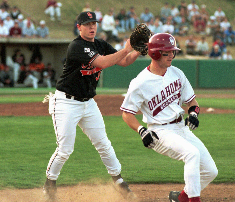 OSU 1st baseman JAMIE COOK makes the tag on OU player DUSTY HANSEN as he heads towards the first base bag after hitting a short ball to the infield during bedlam baseball game. PHOTO FROM THE OKLAHOMAN ARCHIVES