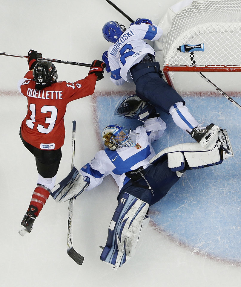 Photo - Goalkeeper Noora Raty lands on her back as she and Jenni Hiirikoski (6) of Finland defend the goal under pressure form Caroline Ouellette (13) of Canada during the 2014 Winter Olympics women's ice hockey game at Shayba Arena, Monday, Feb. 10, 2014, in Sochi, Russia. Canada defeated Finland 3-0. (AP Photo/Matt Slocum)