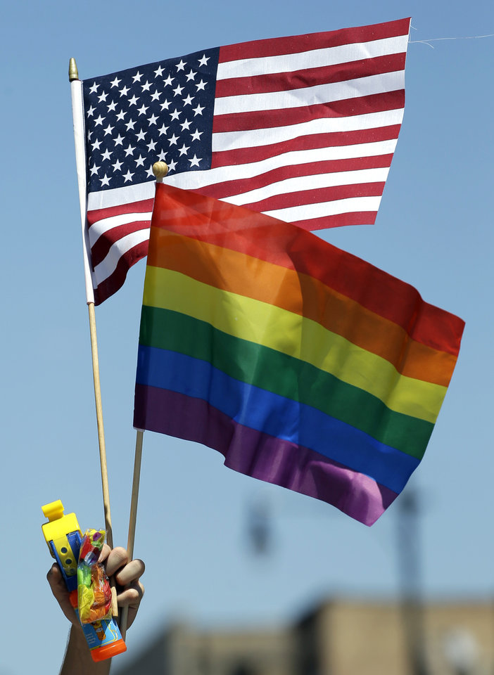 Photo - A participant hold flags at the 45th Annual Chicago Pride Parade during the parade on Broadway Street in Chicago, Sunday, June 29, 2014. The event, the first since Illinois' law allowing same-sex marriage went into effect, has 200 registered entrants, with about 1 million expected to participate. (AP Photo/Nam Y. Huh)