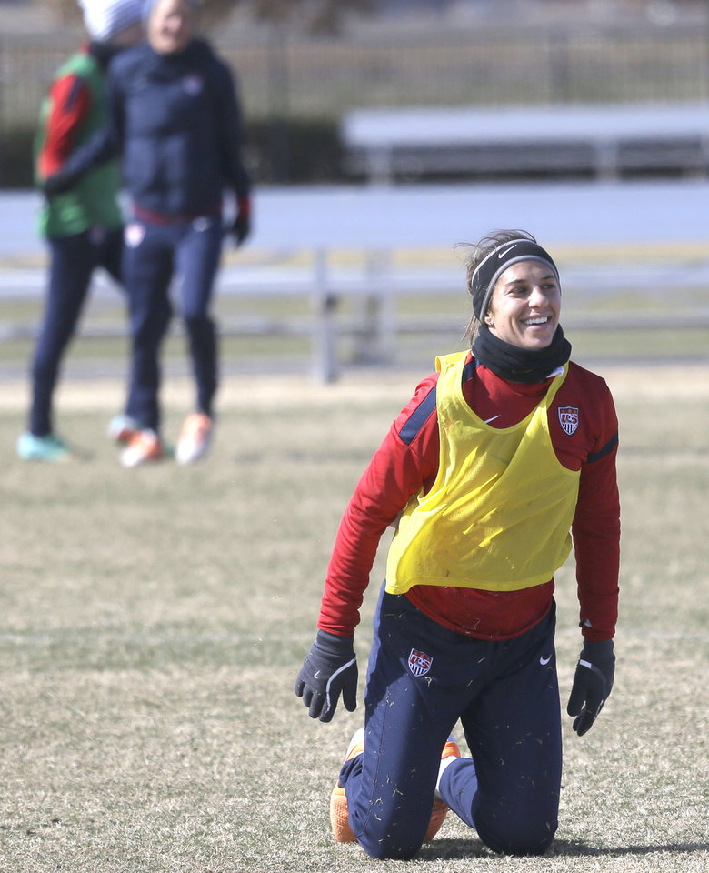 Photo - In this photo made Tuesday, Jan. 28, 2014, U.S. women's soccer team player Carli Lloyd smiles after a fall  during practice in Frisco, Texas. The U.S. women's soccer team opens its season against Canada in Texas on Friday, Jan. 31, their second meeting since the 2012 Olympic match. (AP Photo)