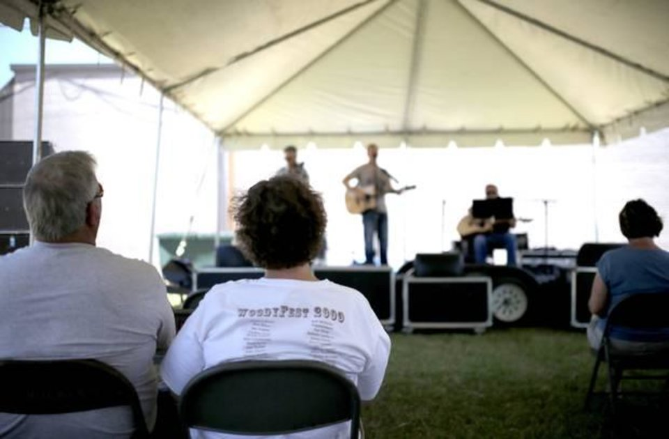 Photo -  People listen to Brent Giddens at the new downtown outdoor venue during the Woody Guthrie Festival in Okemah, Okla., Friday, July 11, 2014. Photo by Sarah Phipps, The Oklahoman