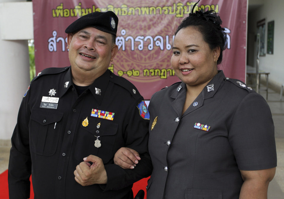 Photo - In this photo taken Thursday, July 4, 2013, two Thai police officers Lt. Winya Thengnimitr, left, and Lt. Col. Anusara Chumchangrua pose for a photograph at a police training center in Bangkok, Thailand. As part of a national effort to reduce the numbers of overweight officers, Thailand has opened a 12-day boot camp to get police into shape. This week, 60 overweight officers from around the country were sent to suburban Bangkok for dawn-to-dusk exercise and lecture programs on living more healthy. (AP Photo/Apichart Weerawong)
