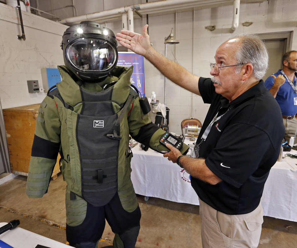 Photo -  A bomb disposal suit and helmet are shown by Johnnie Walden at a vendors' display at the International Association of Bomb Technicians and Investigators regional conference, hosted by the Norman Police Department. [PHOTO BY STEVE SISNEY, THE OKLAHOMAN]