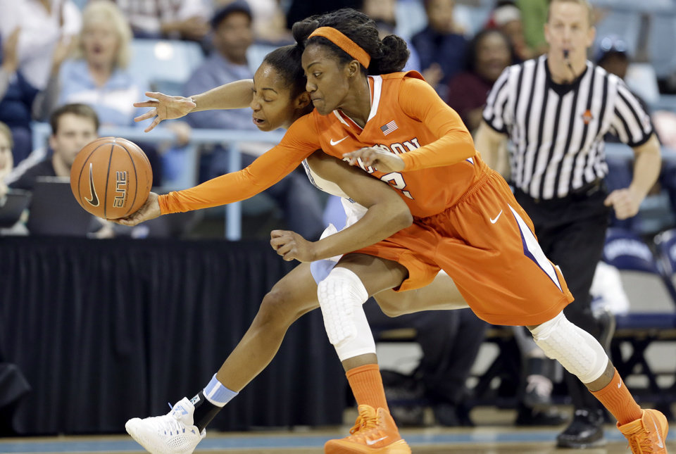 Photo - North Carolina's N'Dea Bryant, left, and Clemson's Chelsea Lindsay, right, reach for a loose ball during the first half of an NCAA college basketball game in Chapel Hill, N.C., Thursday, Jan. 16, 2014. (AP Photo/Gerry Broome)