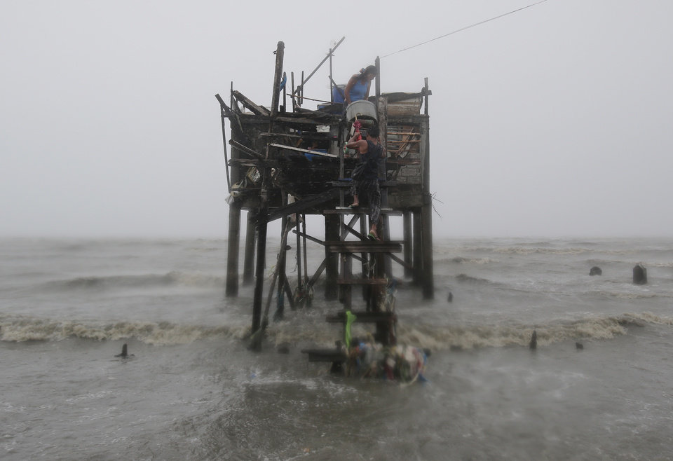 Photo - Residents carry their belongings up their house on stilts as strong winds and rains caused by Typhoon Koppu hits the coastal town of Navotas, north of Manila, Philippines on Sunday, Oct. 18, 2015.  Slow-moving Typhoon Koppu blew ashore with fierce wind in the northeastern Philippines early Sunday, toppling trees and knocking out power and communications. (AP Photo/Aaron Favila)