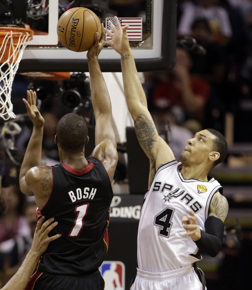 Photo - Miami Heat's Chris Bosh (1) shoots as San Antonio Spurs' Danny Green (4) defends during the first half at Game 4 of the NBA Finals basketball series, Thursday, June 13, 2013, in San Antonio. (AP Photo/Eric Gay)