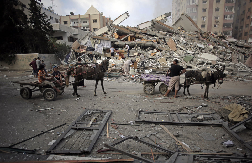 Photo - Palestinians inspect the rubble of the Al-Zafer apartment tower following Saturday Israeli airstrikes that collapsed the 12-story building, in Gaza City, Sunday, Aug. 24, 2014. The targeting of large buildings appears to be part of a new military tactic by Israel. (AP Photo/Khalil Hamra)